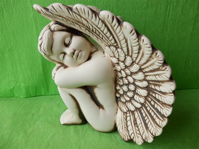 Keramický anděl sedící vlevo